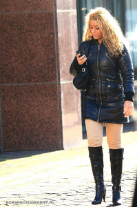a woman wearing winter clothes while texting and walking along the street
